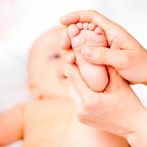 Малышу разминают стопы