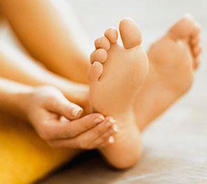 Женщина трогает руками больные стопы