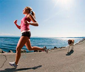 Девушка с собакой бежит по берегу моря