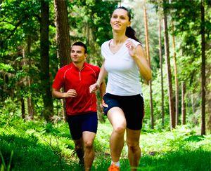 Парень с девушкой бегут по лесу
